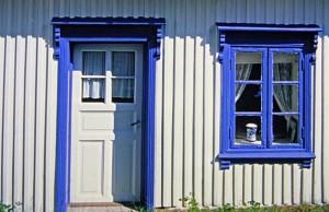 Weißes Holzhaus mit blauen Fenstern