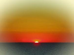 Sonnenuntergang am Kap Arkona im orangenem und goldenem Licht mit schwarzem Meer