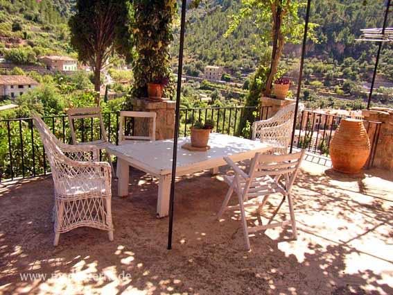 Mallorca - Terrasse einer Bergfinca mit weißem Tisch und Korbsesseln