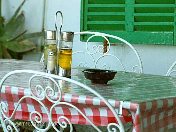Terrassentisch mit Stühlen und Olivenöl-Würzfläschchen auf Mallorca