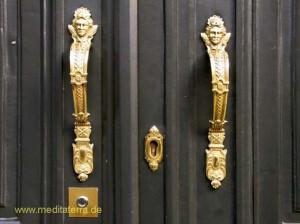 Schöne Haustür in Brüssel mit goldenen Türgriffen und kleinen Köpfen verziert