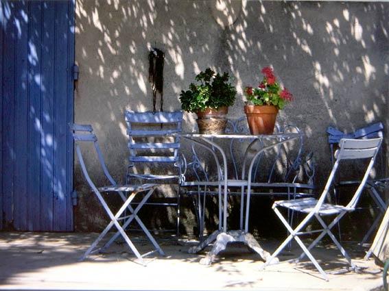 Provence-Haus: Terrasse mit hellblauen Gartenstühlen und runden taubenblauen Tisch mit Blumentöpfen