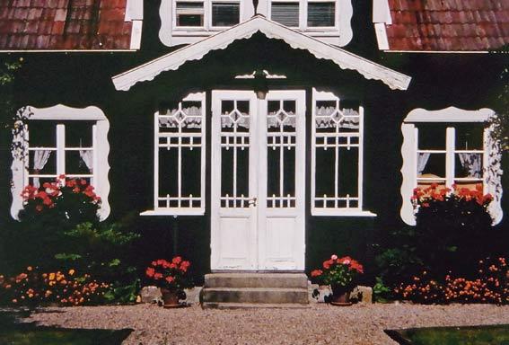 Schwarzes Holzhaus in Schweden - Eingangsveranda mit weißen Verzierungen