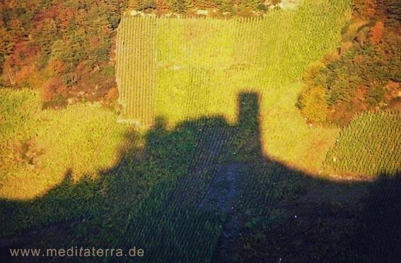 Schattenspiel einer Moselburg mit Weinbergen im Herbst