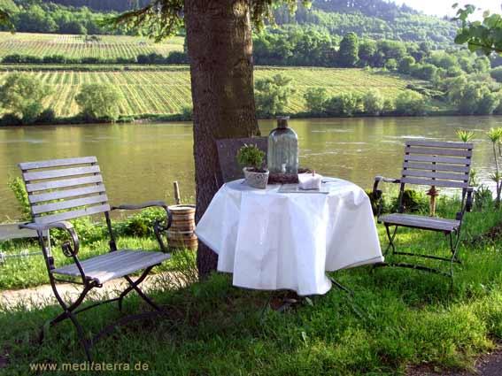 Mosel mit Weinbergen und Tisch mit zwei Stühlen