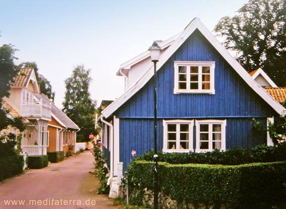 Blaues Holzhaus in Arild und weitere farbenfrohe Holzhäuser in der Straße