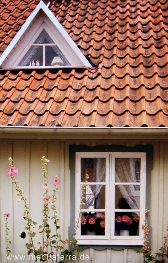 Fenster und Dreiecksgaube an einem Holzhaus in Schweden