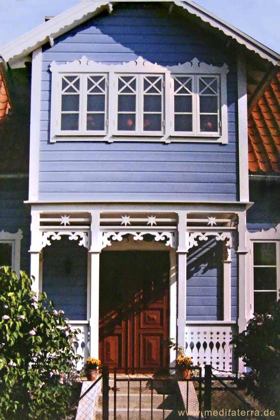 Blaues Holzhaus mit schönen Verzierungen an den Fenstern und in der Eingangsveranda