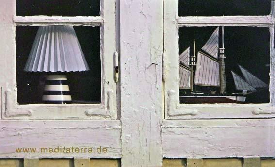 Fenster an einem schwedischen Holzhaus mit Lampe und Schiff