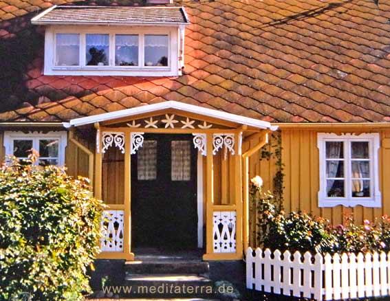 Gelbes Holzhaus in Schweden mit filigraner Eingangsveranda