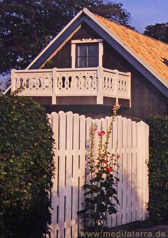 Schwedisches Sommerhaus mit weißem Balkon und weißem Gartentor und Malven