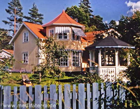 Gelbes Holzhaus mit Türmchen und weißem Gartenpavillon in Schweden