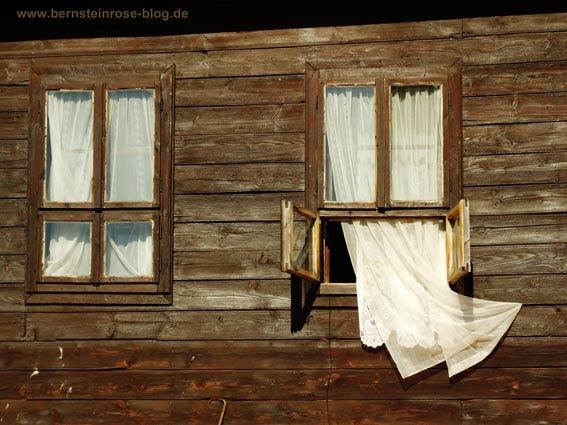 Achtsamkeitstraining: Fenster mit wehender Gardine an einem Holzhaus im Süden.