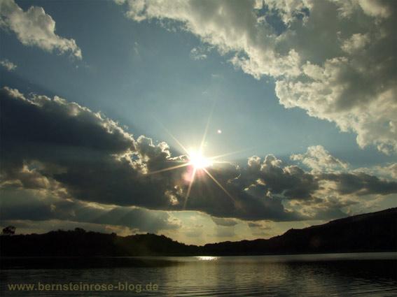 Golden glitzernder See mit schillernder Sonne und Wolken.