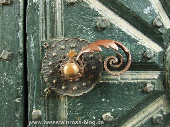 antiquierte Türklinke an einer dunkelgrünen Holztür mit kleinem Kreuz am Griff