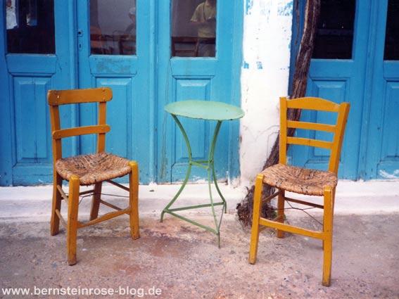 Insel Kreta: zwei Korbstühle mit grünem Kaffeetisch vor blauen Türen