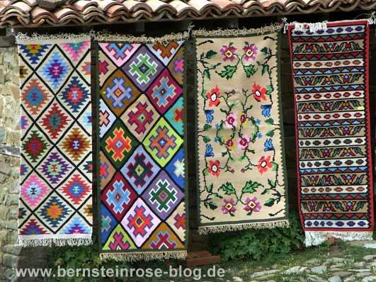 vier farbenfrohe Teppiche an einer Mauer aufgehangen - verschiedene Muster