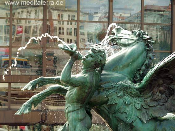 Gewandhausbrunnen in Leipzig: Im Hintergrund das Gewandhaus mit dem Spiegelbild des Opernhauses am Augustusplatz
