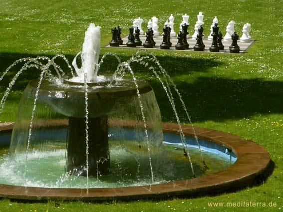 Springbrunnen mit Schachspiel im Hintergrund auf einer Wiese