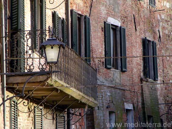 Schmiedeeiserner Balkon und alte Laterne an einem Toskana-Haus in Montepulciano - Nähe Stadtmauer