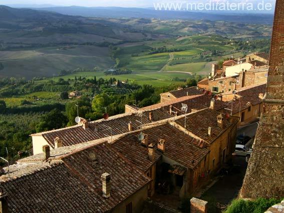 Blick von der Stadtmauer in Montepulciano in der Toskana auf alte Gemäuer und die Weinberge hinweg