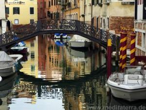 Brücke in Venedig mit bunter Wasserspiegelung und Booten