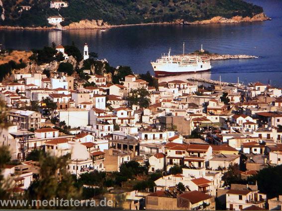 Blick auf die Hautpstadt der Insel Skiathos mit weißem Schiff im Hafen und Inselchen drumherum