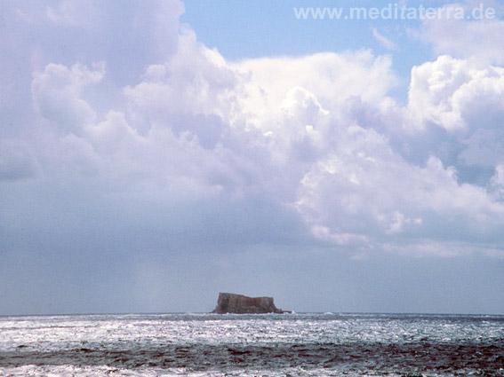 Romantischer Blick zum Felsenriff Filfla mit Wolken vor der Südküse Maltas