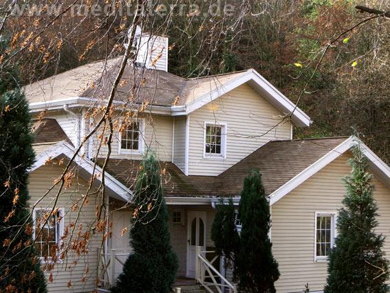 Beiges Holzhaus mit Zypressen im amerikanischen Stil