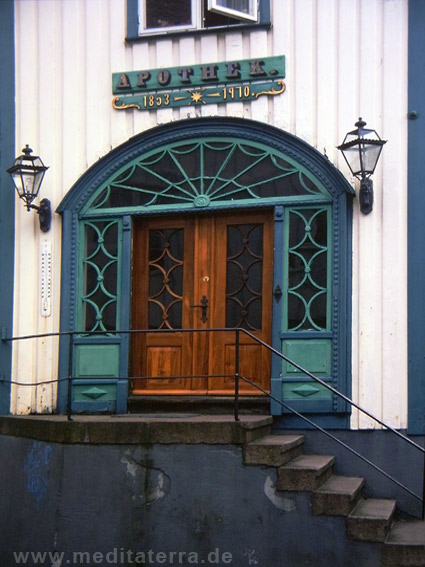 Holzhaus mit türkiser Eingangsgestaltung im Jugendstil