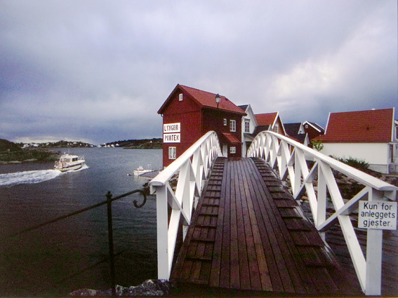 Holzbrücke zu einer Schäreninsel mit Holzhaussiedlung in Norwegen