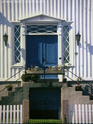 Blaue Haustür an einem weißen Holzhaus in Norwegen