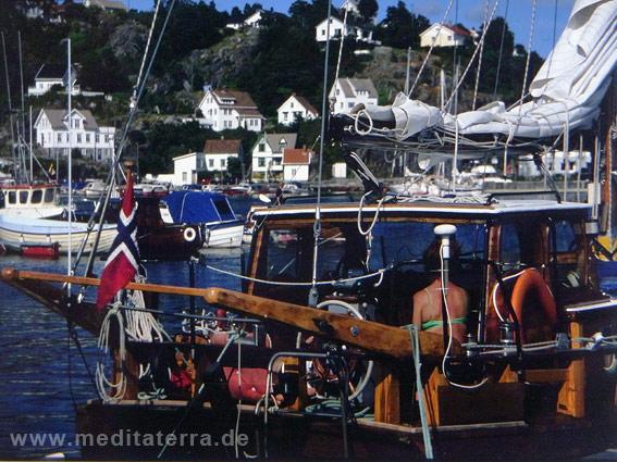 Blaues Meer mit Segelyacht und weißen Häusern in Norwegen
