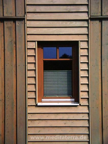 Grüne Holzhausfassade mit kleinem Fenster