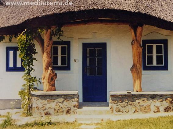 Bauernhaus in Südosteuropa mit Reetdach und blau bemalten Fenstern