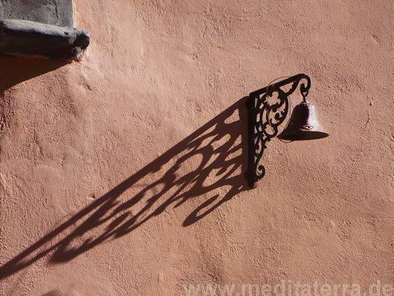 Glocke mnit Schatten an oranger Hauswand
