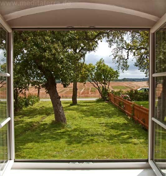 Offenes Fenster mit Blick auf Garten und Landschaft