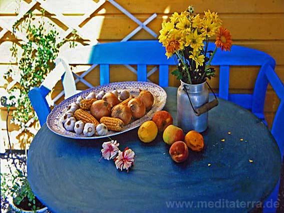 Türkiser Terrrassentisch mit blauer Bank und Obstschale