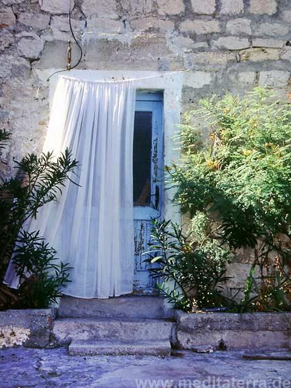 Dalmatinisches Steinhaus mit blauer Tür und Gardine